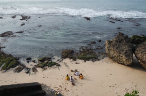 A small and secluded beach lowers down into the sea. A group of people are sitting on the sand relaxing.